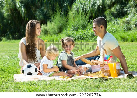 happy parents with little daughters having holiday with picnic - stock photo