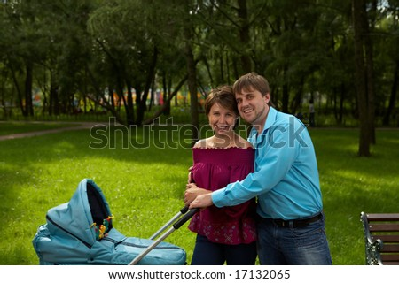 Happy parents with newborn in a pram walk in park