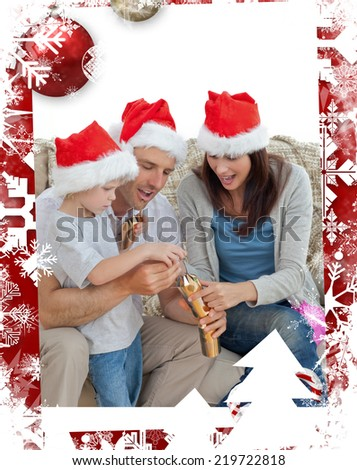 Happy parents with son opening crackers together against christmas themed frame