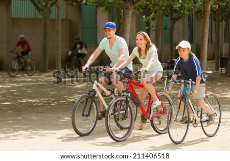 Happy parents with teenager son going by bicycles through city in summer day - stock photo