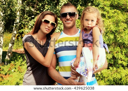 Happy parents with their adorable little daughter. Outdoors. Sunny summer day. - stock photo