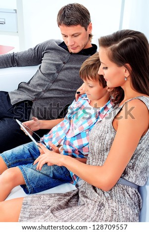 Happy parents with their son looking at touchpad pc together at home.