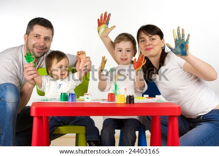 Happy parents with thier childern enjoy painting with assorted colours on hands - stock photo