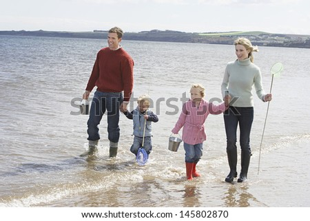 Happy parents with two children enjoying vacation on beach - stock photo