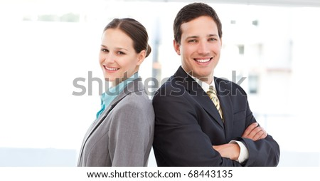 Happy partners posing together back to back at work - stock photo
