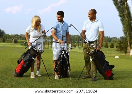 Happy partners standing on golf course, choosing golf club from golfing kit, starting game. - stock photo