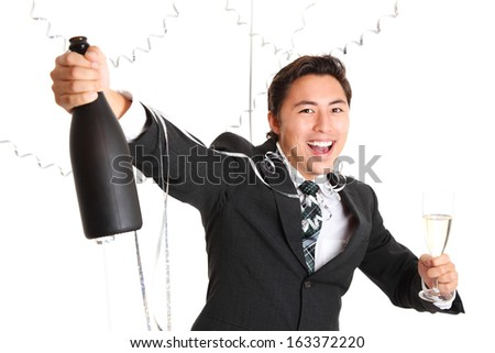 Happy party guy with champagne bottle wearing a suit and tie. White background. - stock photo