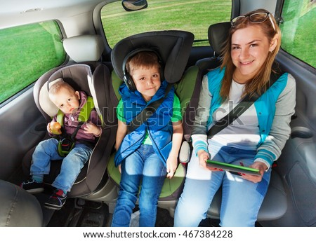Happy passengers sitting on the backseats of a car