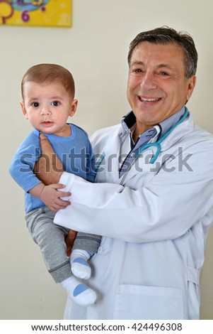 Happy pediatric doctor holding an healthy baby boy after examination control. - stock photo