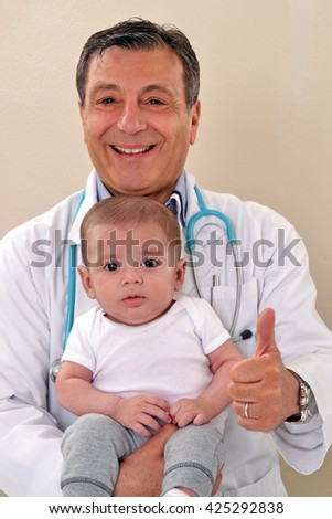 Happy pediatrician doctor holding an healthy baby boy after examination control.Making positive sign with hand. - stock photo