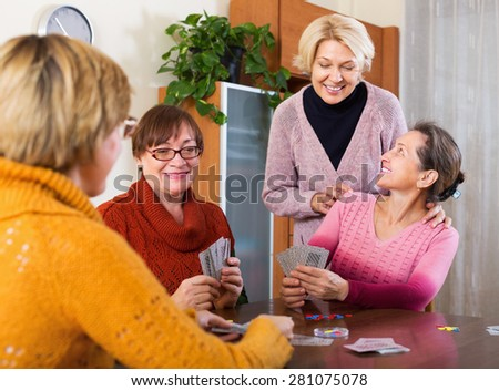 Happy pensioners having fun with pack of cards indoor - stock photo