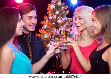 Happy people clinking by glases around the Christmas tree - stock photo