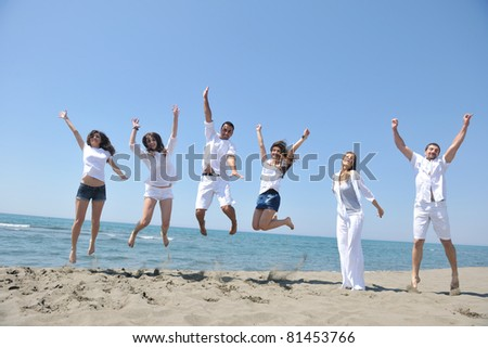 happy people group have fun  run and jump  on beach beautiful sand  beach - stock photo