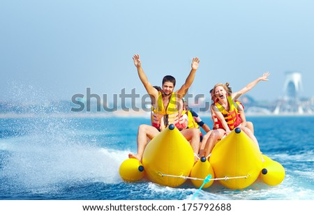 happy people having fun on banana boat - stock photo