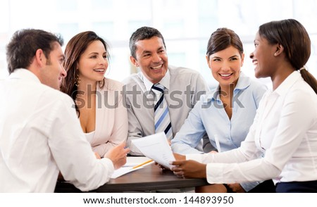 Happy people in a business meeting at the office smiling - stock photo