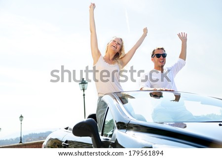 Happy people in car driving on road trip. Young couple having fun dancing and cheering in car driving on travel vacation together. Lifestyle with beautiful cheerful lovers, young woman and man. - stock photo
