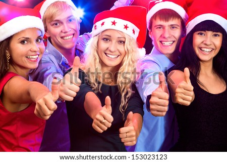 Happy people in santa hat show thumb up