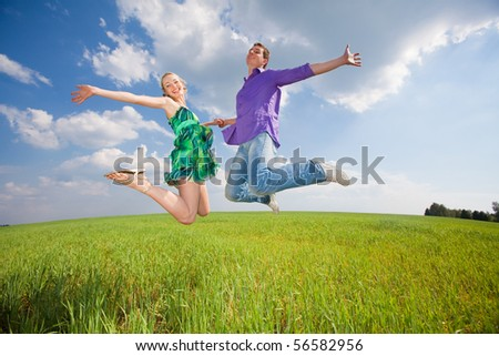 Happy people is jumping in field
