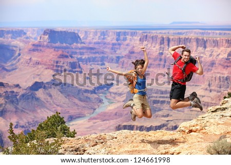 Happy people jumping in Grand Canyon. Young multiethnic couple on hiking travel. Grand Canyon, south rim, Arizona, USA. - stock photo