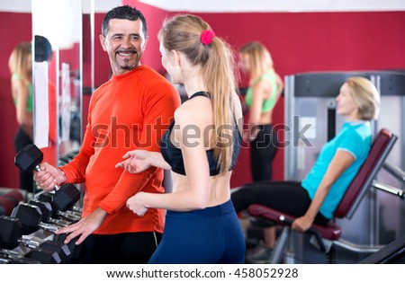 Happy people of different age having strength training in sport club