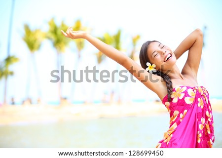 Happy people on beach travel - woman in sarong cheerful in happiness during summer vacation holidays on Hawaii. Multiracial Caucasian / Asian female girl. - stock photo