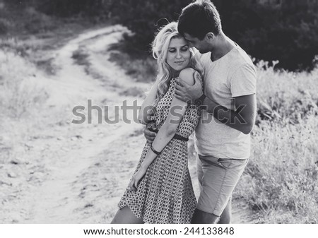 Happy people outdoors beautiful landscape and couple in love with flowers on sunset happy people outdoor go away back black and white - stock photo