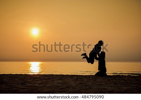Happy people playing on the sunset beach