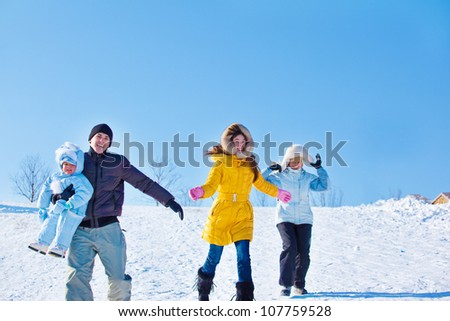 Happy people running down winter hill - stock photo