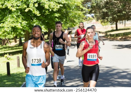 Happy people running race in park on a sunny day - stock photo