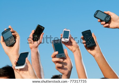 Happy people showing their modern mobile phones against blue sky - stock photo