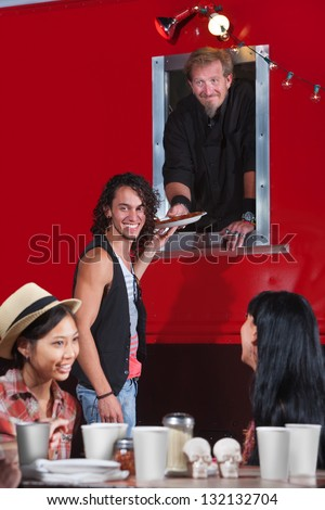 Happy people waiting for pizza from food truck - stock photo