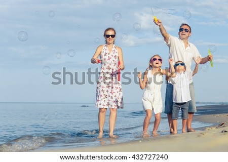 Happy people walking on the beach at the day time. Concept of friendly family.