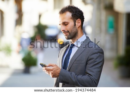 Happy people with businessman on the phone typing text message in city street - stock photo