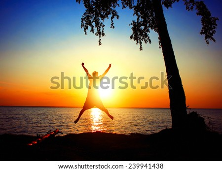 happy person jumping on the sunset sky background - stock photo