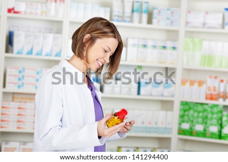Happy pharmacist chemist woman working in pharmacy drugstore - stock photo