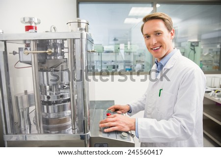 Happy pharmacist pressing button on machine at the hospital pharmacy
