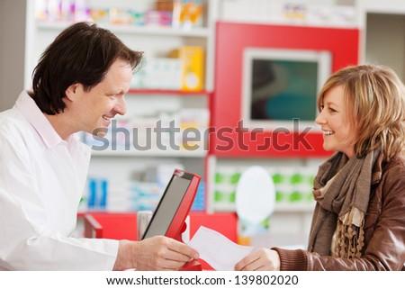 Happy pharmacist receiving prescription paper from customer in pharmacy - stock photo