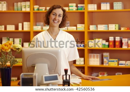 Happy pharmacist standing behind counter in pharmacy - stock photo