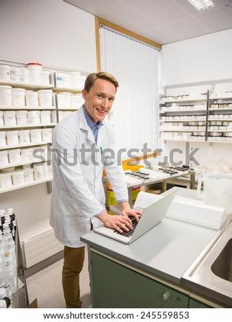 Happy pharmacist using his laptop at the hospital pharmacy
