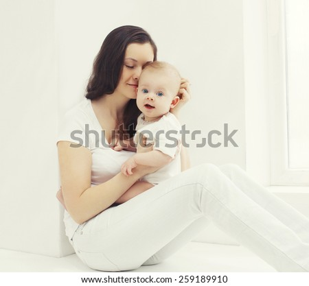 Happy photo young mother with baby at home in white room near window - stock photo