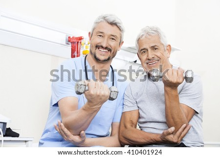 Happy Physiotherapist And Senior Patient Lifting Dumbbells - stock photo