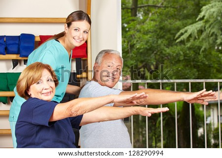 Happy physiotherapist with seniors doing fitness exercises for their backs - stock photo
