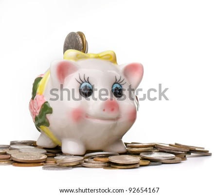 happy piggy bank on a pile of coins - stock photo