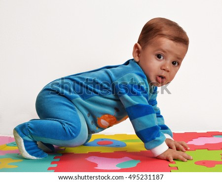 Happy playful baby playing on rubber foam carpet.