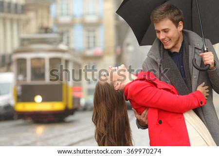 Happy playful couple in love dating joking and laughing in the street of an old town in a rainy day under an umbrella - stock photo