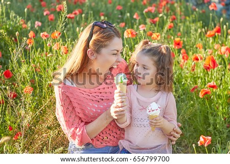 Happy Playful family. Young beautiful  mother and her daughter having fun, and Eat ice cream. Positive human emotions, feelings, joy.