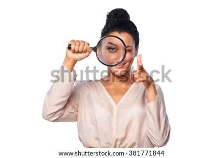 Happy playful female looking through a magnifying glass, giving a wink and pointing her finger at camera, over white background