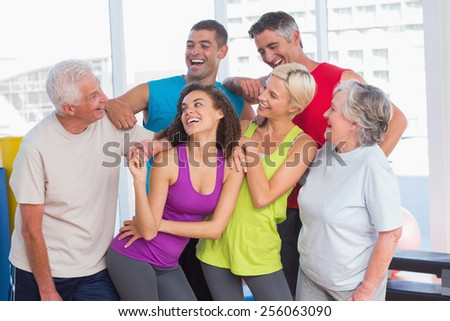 Happy playful friends looking at senior man at fitness studio