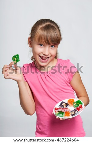 Happy playful little girl holding a plate with colorful jelly candies sweets Turkish delights