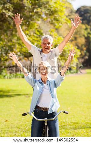 happy playful senior couple having fun riding bicycle outdoors - stock photo